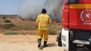 A fire fighter at the scene of a blaze caused by incendiary balloons sent from nearby Gaza
