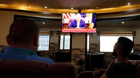 Palestinians in the West Bank city of Hebron watch as U.S. President Donald Trump announces the UAE-Israel agreement to normalize relations