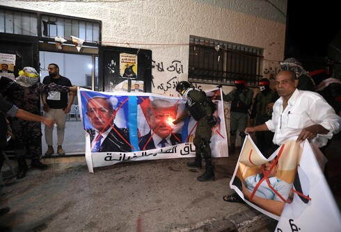 Palestinians burn banners depicting Abu Dhabi Crown Prince Mohammed bin Zayed al-Nahyan (R), Israeli Prime Minister Benjamin Netanyahu (L) and US President Donald J. Trump (C), during a protest against the peace agreement