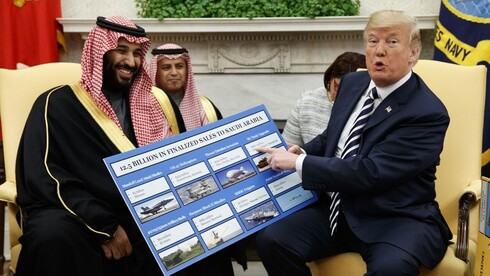President Donald Trump shows a chart highlighting arms sales to Saudi Arabia during a meeting with Saudi Crown Prince Mohammed bin Salman in the Oval Office of the White House in Washington