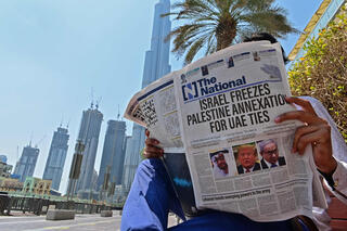 man reading a copy of  the UAE-based The National newspaper regarding the UAE-Israel agreement