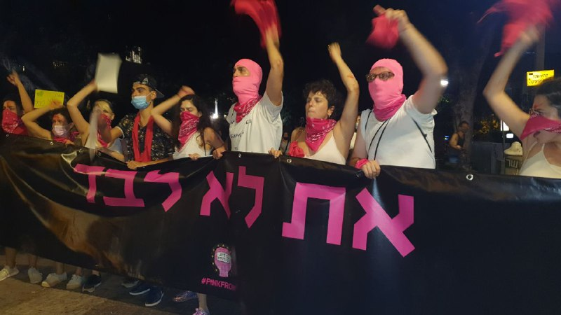 Protesters in Tel Aviv over mass rape of a 16-year-old girl carry a banner reading: You are not alone