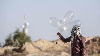 A terrorist in Gaza prepares to launch an incendiary device towards Israel using what appear to be condoms filled with helium