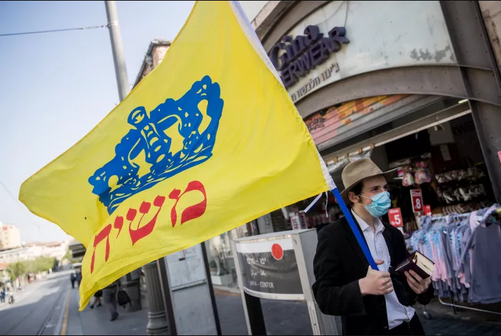 Illustrative: A man holds a Chabad flag on Jaffa street in downtown Jerusalem on April 20, 2020