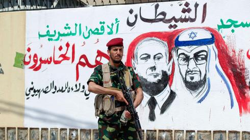 A fighter loyal to Yemen's Huthi rebels stands guard next to a mural denouncing Abu Dhabi Crown Prince Sheikh Mohammed bin Zayed Al Nahyan (R) and Israeli Prime Minister Benjamin Netanyahu