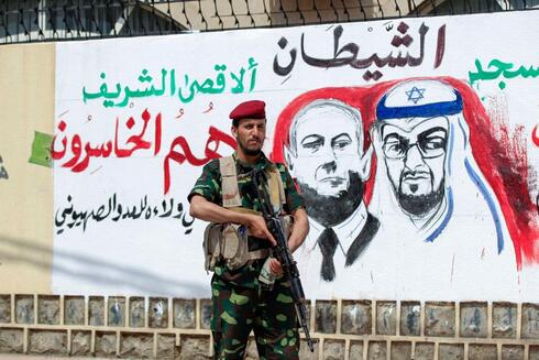 A Houthi fighter stands next to a mural in Yemen's capital Sanaa denouncing the UAE and Israeli leaders for their new bilateral ties