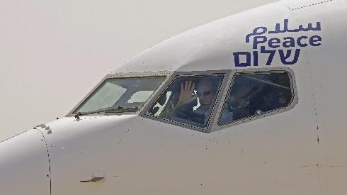 The captain of the El Al airliner which will carry US and Israeli delegations to the United Arab Emirates waves to spectators as the plane prepares to take off on the first-ever commercial flight from Israel to the UAE