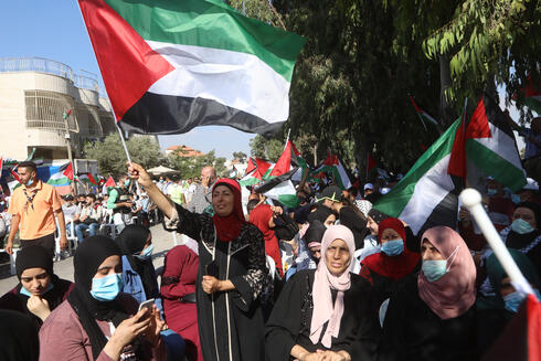 Palestinians wave national flags during a protest against the peace agreement to establish diplomatic ties between Israel and the United Arab Emirates