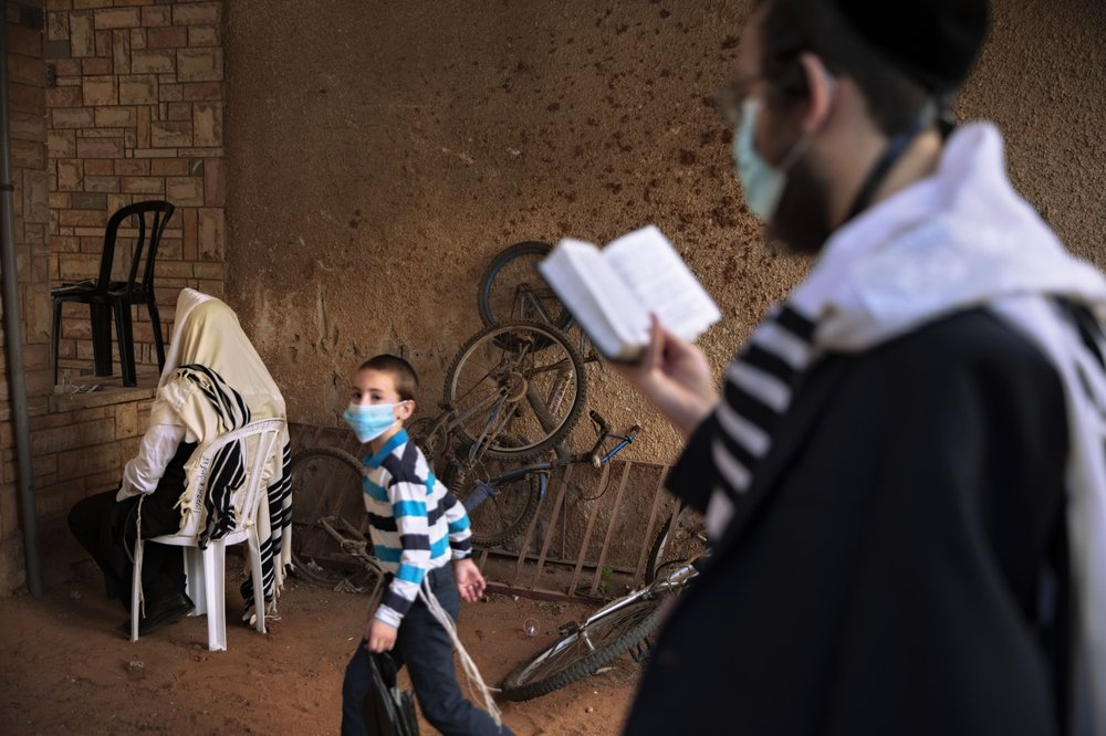 ultra-Orthodox Jews pray a morning prayer next to their house as synagogues limited to twenty people following the government's measures to help stop the spread of the coronavirus in Bnei Brak, Israel