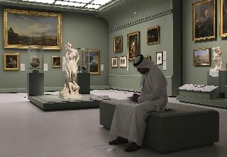 An Emirati man next to the Bather, also called Venus statue by Christophe-Gabriel Allegrain, 1710-1795, at the Louvre Museum in Abu Dhabi, United Arab Emirates