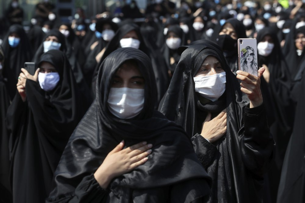 people wearing protective face masks to help prevent spread of the coronavirus mourn during an annual ceremony commemorating Ashoura in Tehran, Iran
