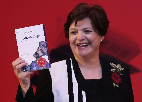 Sahar Khalifeh chair of the Arab fiction judges announces the winning writer, Mohammed Hasan Alwan, Saudi Arabia's novelist, as she shows his book, A Small Death, during the International Prize for Arabic Fiction (IPAF) in Abu Dhabi, United Arab Emirates