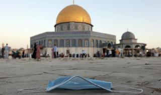 a protective face mask is left on the ground during the Eid al-Adha prayers, next to the Dome of the Rock Mosque in the Al Aqsa Mosque compound in Jerusalem's Old City