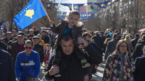 A father holds his son waving Kosovo's flag as they celebrate the 12th anniversary of the country's independence, in the capital Pristina, Monday, Feb. 17, 2020