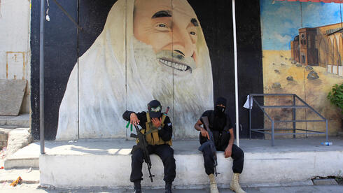 Militants from the Palestinian group Hamas, sit in front of a mural depicting late Hamas leader Ahmed Yassin, as the group's top leader, Ismail Haniyeh, visits at Ain el Hilweh Palestinian refugee camp in Sidon, Lebanon