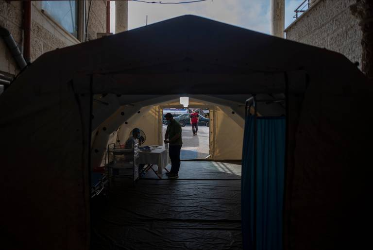 A Palestinian medic checks a person's temperature to screen for coronavirus symptoms, inside a temporary tent at the entrance al-Quds Hospital, in Gaza City