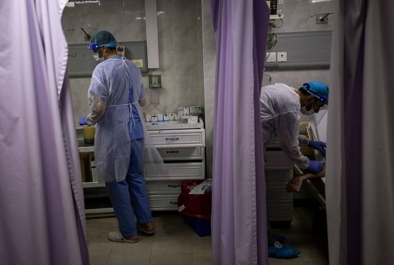 Palestinian doctors treat patients at the emergency room of the al-Quds Hospital in Gaza City