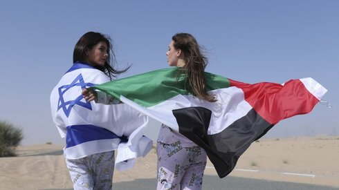 Israeli model May Tager, left, covers herself with an Israeli flag next to Anastasia Bandarenka, a Dubai-based model who wraps herself in a UAE flag during a photo shoot in Dubai, United Arab Emirates