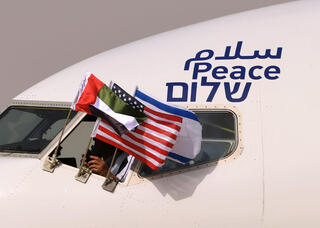 The Emirati, Israeli and U.S. flags fly from the window of an El Al plane adorned with the word 'peace' in Arabic, English and Hebrew, as it lands in Abu Dhabi