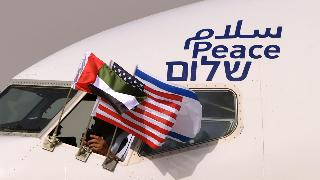 """the Emirati, Israeli and US flags are picture attached to an air-plane of Israel's El Al, adorned with the word """"peace"""" in Arabic, English and Hebrew"""
