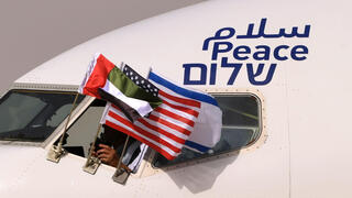 """UAE, Israeli and U.S. flags hoisted outside an El Al airplane, adorned with the word """"peace"""" in Arabic, English and Hebrew"""