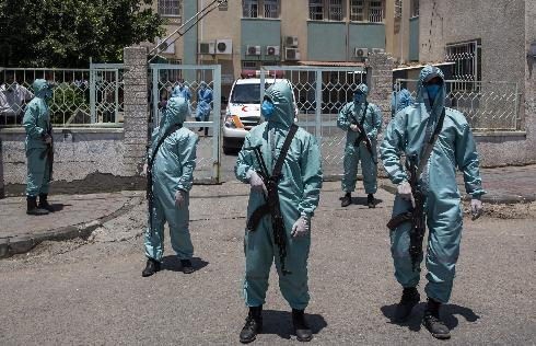 Gaza security men in protective gear outside local hospital