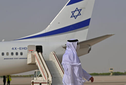 An Emirati official stands near an air-plane of El Al, which carried a US-Israeli delegation to the UAE following a normalisation accord, upon it's arrival at the Abu Dhabi airport