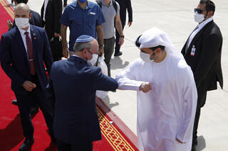 National Security Advisor Meir Ben-Shabbat elbow bumps with an Emirati official during a visit by an Israeli delegation to Abu Dhabi, Sept. 2020