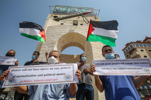 Palestinians carry placards during a protest in Rafah in the southern Gaza Strip, on September 12, 2020, to condemn the normalisation of ties between Israeli and Bahrain