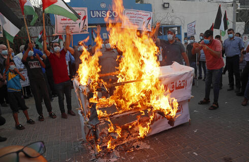 Palestinians burn mock coffins representing the United Arab Emirates and Bahraini normalization agreements with Israel