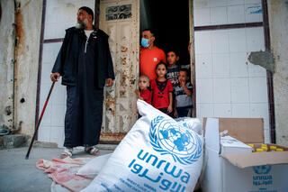 Members of a Palestinian family, some clad in mask due to the COVID-19 coronavirus pandemic, stand through the door of their home as they receive food aid provided by the United Nations Relief and Works Agency for Palestine Refugees (UNRWA) in Gaza