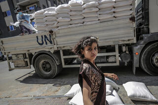 A Palestinian child waits to for food supplies with her family from the United Nation Relief and Works Agency (UNRWA)