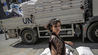 A Palestinian child waits to recieve food applies with her family from the United Nation Relief and Works Agency (UNRWA)