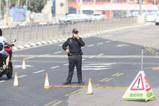 Police place a roadblock across a main Tel Aviv road during the closure that began Friday