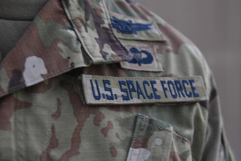 Capt. Ryan Vickers stands for a photo to display his new service tapes after taking his oath of office to transfer from the U.S. Air Force to the U.S. Space Force at Al-Udeid Air Base, Qatar