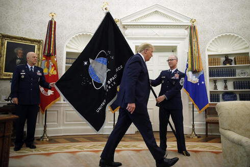 Chief of Space Operations at United States Space Force Gen. John Raymond, left, and Chief Master Sgt. Roger Towberman, right, hold the U.S. Space Force flagֲ as President Donald Trump walks past it, in the Oval Office of the White House in Washington