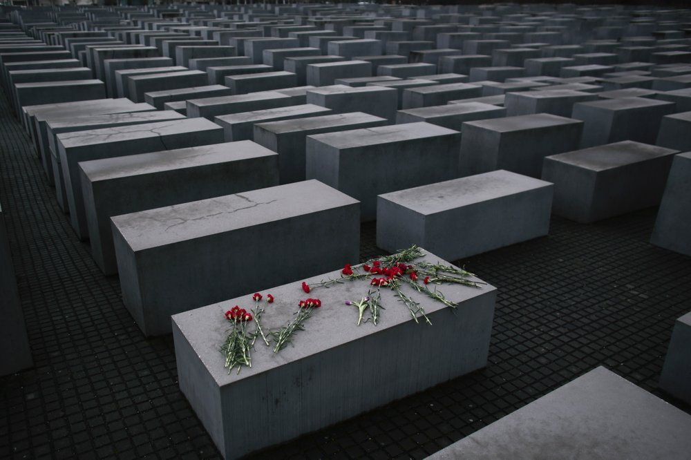 flowers lie on a concrete slab of the Holocaust Memorial to mark the International Holocaust Remembrance Day and commemorating the 70th anniversary of the liberation of the Nazi Auschwitz death camp in Berlin