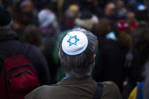 A man wears a Yamaka, as he attends a demonstration against an anti-Semitic attack in Berlin