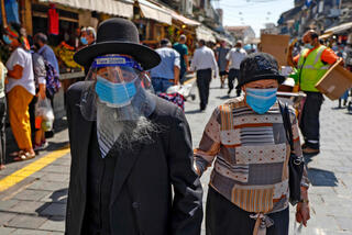 An Israeli couple wears face masks during a visit to Mahane Yehuda market in Jerusalem