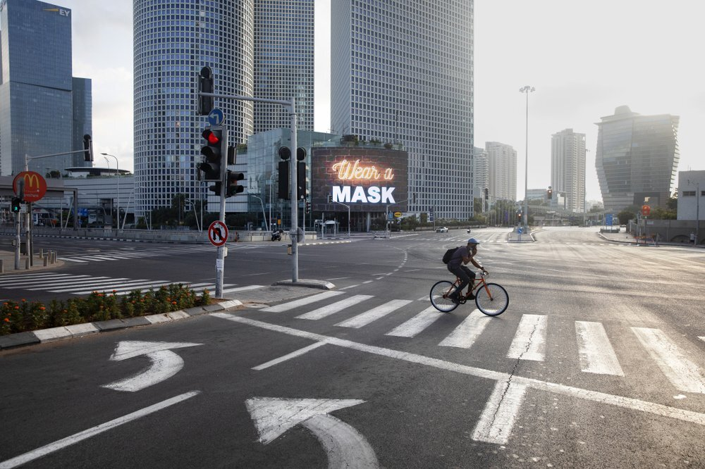 A man rides a bicycle next to a billboard calling people to wear masks, on empty road following new restrictions in the three-week nationwide lockdown, in Tel Aviv