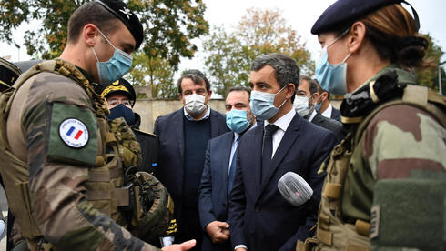 French Interior Minister Gerald Darmanin, center left, Joel Mergui, center left behind , President of the Israelite Central Consistory of France talk with soldiers before a visit to the synagogue of Boulogne-Billancourt