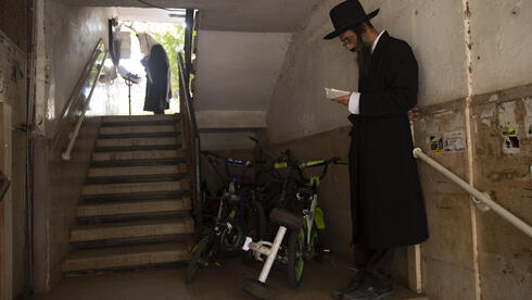 Ultra-Orthodox Jews keep social distancing and wear face masks during a morning prayer next to their houses as synagogues are limited to twenty people due to the coronavirus pandemic, in Bnei Brak