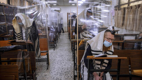 In this Monday, Sept 21, 2020 file photo, ultra-Orthodox Jews wear face masks during a morning prayer in a synagogue separated by plastic partitions, in Bnei Brak