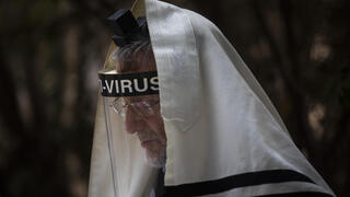 An ultra-Orthodox Jewish man wears a face mask during a morning prayer next to his house as synagogues are limited to twenty people due to the coronavirus pandemic, in Bnei Brak