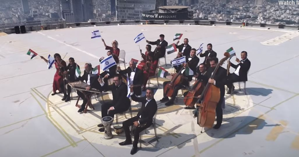 The Firqat Alnoor Orchestra waves israeli and Emirati flags as it performs a musical tribute to new bilateral ties