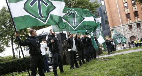 Supporters of the neo-Nazi Nordic Resistance Movement hold flags during a demonstration at the Kungsholmstorg square in Stockholm