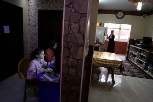 Palestinian sisters Raseel and Mariam Hussein attend their online lessons as their mother Yasmine works in their home kitchen, amid the coronavirus disease (COVID-19) outbreak, in Gaza City