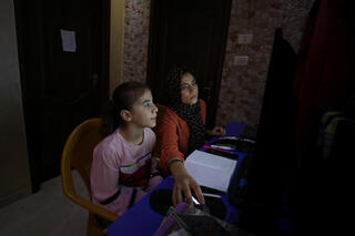 Palestinian sisters Raseel and Mariam Hussein attend their online lessons in their home, amid the coronavirus disease (COVID-19) outbreak, in Gaza City
