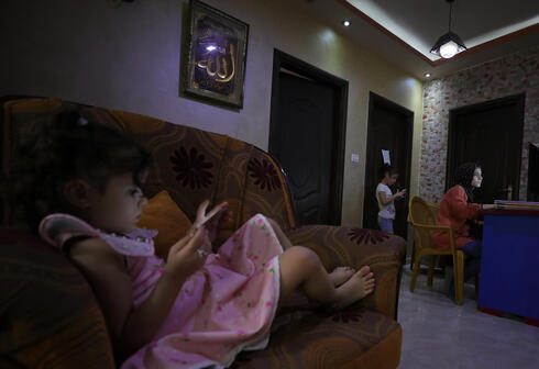 Palestinian student Raseel Hussein attends an online lesson as her sisters play with mobile phones in their family home, amid the coronavirus disease (COVID-19) outbreak, in Gaza City