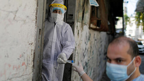 Palestinian healthcare workers leave a home after collecting swab samples from a family to be tested for the coronavirus disease (COVID-19), in Gaza City